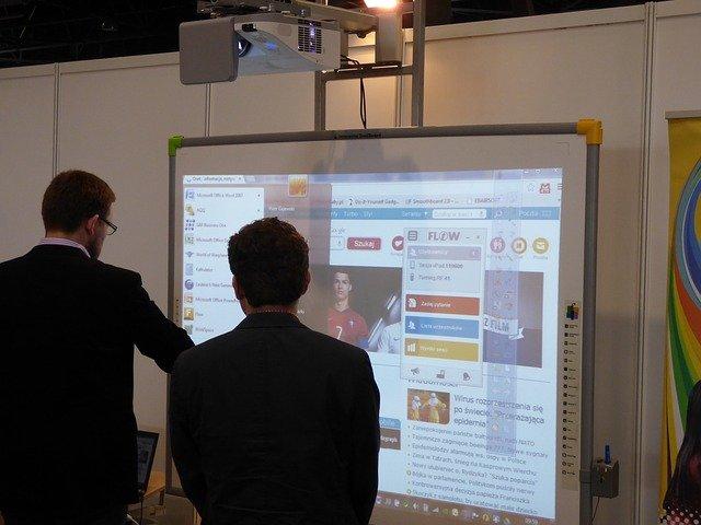 dva muži před interaktivní tabulí