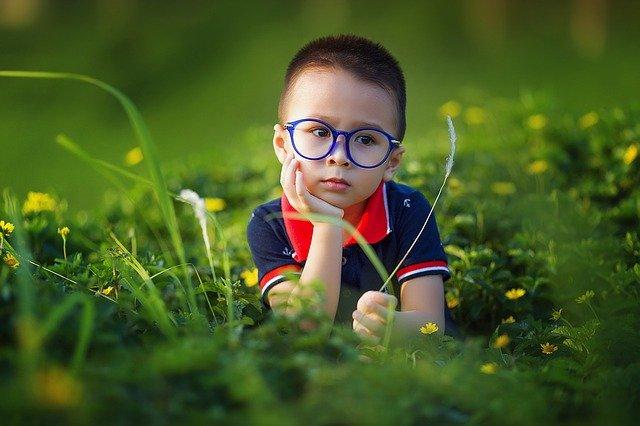 brýlatý chlapec v trávě