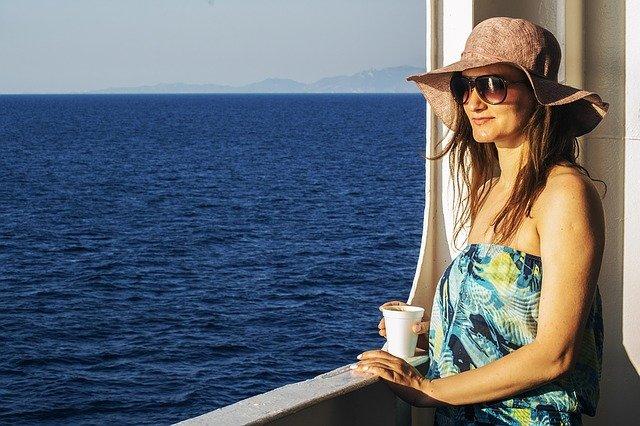 žena s kávou u výhledu na moře
