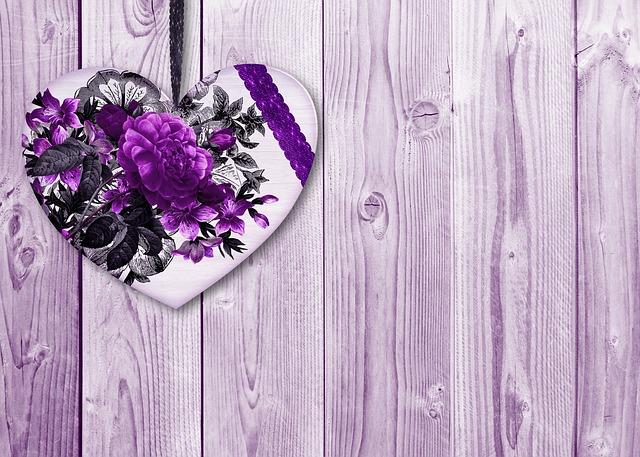 design srdce, které má na sobě květinovou dekoraci do fialové barvy a pozadí je dřevěné