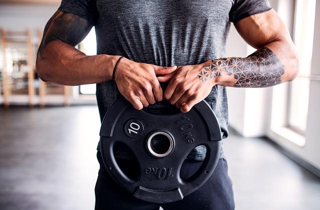 muž v tělocvičně drží závaží