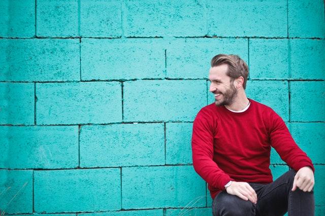 Usmívající se muž sedící před betonovou zdí