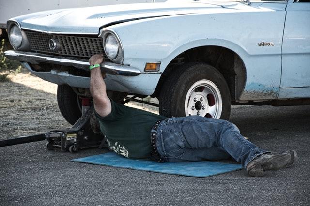 muž pracující pod automobilem