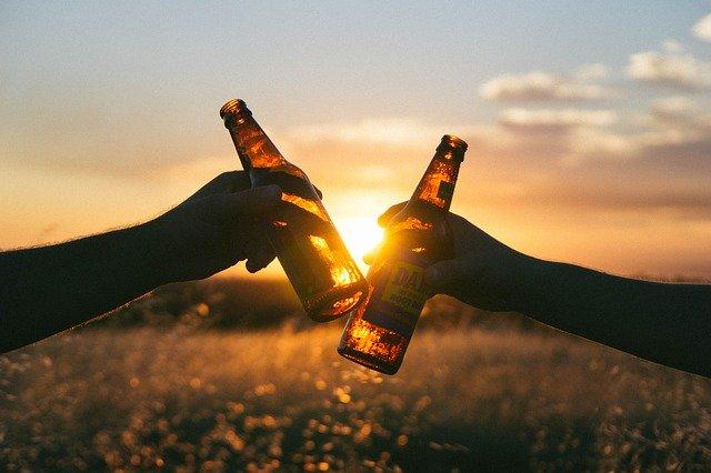 dva lidé přiťukávající si pivem