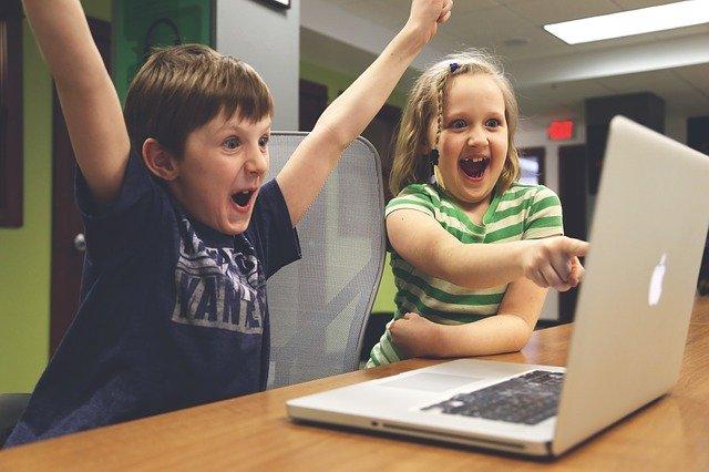 dvě děti radující se u notebooku